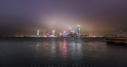 Tsim Sha Tsui on a foggy night with ICC building (the far left) half covered by the fog. Overlooking from Wan Chai in Hong Kong island.