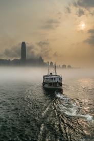 Low fog covering the surface of the ocean in Victoria Harbour right before sunset. Some of the iconic skyscrapers standing up above the fog on the otherside on the harbour on Hong Kong island