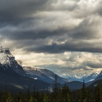 For some reason, these giant peaks looking like they are sitting around a smalll little table in the valley having an important meeting. Don't they? Cloudy morning in the Canadian Rockies. Looking in to the valley surrounded by all these giantic peaks covered by some heavy dense clouds. Sunlights finding their way through the little cracks in the clouds on the horizon. Lighten up some of the peaks showing their beauty. Thank you and have a great day!