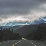 Morning ride with stormy cloudy sky along the Icefields Parkway in the Canadian Rockies. With a little break from the foggy weather on the horizon